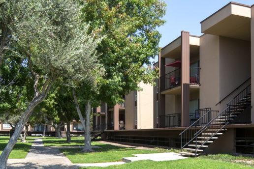 Exterior of building with balconies, sidewalks, trees